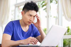 Worried Young Chinese Man Using Laptop At Home Stock Images