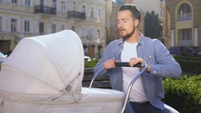 Worried young father trying to calm down newborn swinging baby pram in park stock video