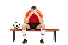 Worried young football player sitting on a bench Royalty Free Stock Images