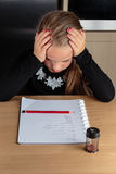 Worried young girl doing homework at the kitchen table royalty free stock image