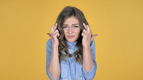Worried Young Girl Standing with Finger Crossed for Good Luck on Yellow Background stock video footage