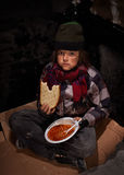Worried young homeless boy eating charity food. Sitting on a cardboard piece stock photos