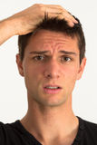Worried young man with hand on face. And frustrated expression Royalty Free Stock Image