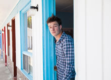 Young man looks out of the motel room Stock Images