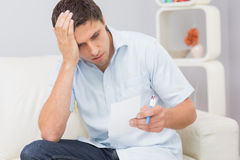Worried young man paying his bills at home Royalty Free Stock Photography