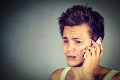 Worried young man talking on phone to someone looking upset Royalty Free Stock Images
