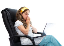Worried young nurse looking in her notebook sitting in armchair Royalty Free Stock Image