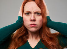 Worried young redhead woman covering ears with hands royalty free stock image