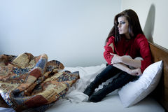 Worried Young Woman. A worried and afraid young woman in bed Royalty Free Stock Image