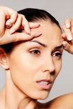 Worried young woman checking wrinkles on forehead stock image