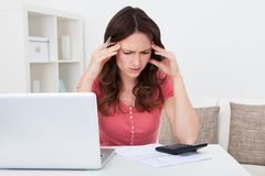 Worried young woman doing calculations Royalty Free Stock Photo