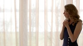 Worried young woman. Girl looking out the window. Love and anxiety stock video footage