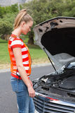 Worried young woman beside her broken down car Royalty Free Stock Photo