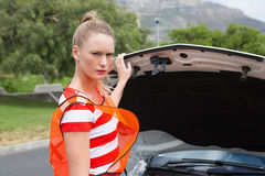 Worried young woman beside her broken down car Royalty Free Stock Photos