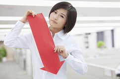 Worried young woman holding arrow sign paper cut out pointing down, indoors office Stock Image