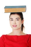 Worried young woman holding book on her head Royalty Free Stock Image