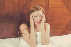 Worried young woman laying in bed can't fall asleep has headache royalty free stock photography