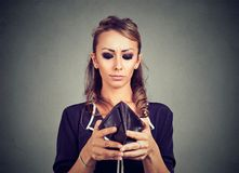 Worried woman looking into her empty wallet stock photo