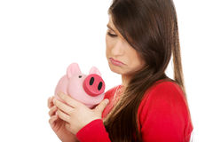 Worried young woman with piggybank. Royalty Free Stock Photos