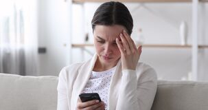 Worried young woman reading bad news in message on smartphone