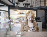 Worried young woman reading text message on cell phone in cafe Stock Photos