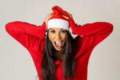 Worried young woman in santa clause hat screaming in stress running out of time for christmas stock image