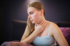 Worried young woman sits on bed alone and looks down. She holds hand on neck. Woman feels pain there. royalty free stock image