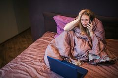 Worried young woman sits on bed and talks on phone. She holds one hand on head. Woman looks at laptop`s sceen. She stock photography