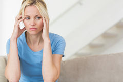 Worried young woman sitting in the living room Royalty Free Stock Photo