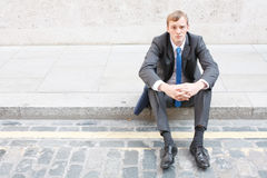 Worries. A worried business man sitting on some stairs Stock Photo