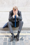 Worries. A worried business man sitting on some stairs Stock Images