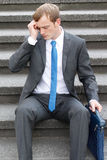 Worries. A worried business man sitting on some stairs Royalty Free Stock Images