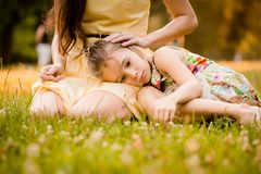 Worries of childhood. Mother is caressing her worried child outdoor in nature Royalty Free Stock Image