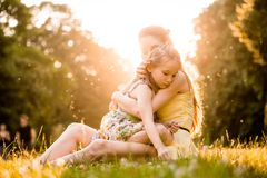 Worries of childhood. Mother is cuddling her worried child outdoor in nature Royalty Free Stock Image