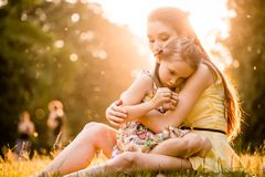Worries of childhood. Mother is cuddling her worried child outdoor in nature Stock Images