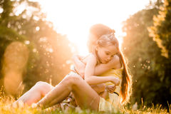 Worries of childhood. Mother is cuddling her worried child outdoor in nature Stock Photos