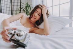 Worring ung asiatisk kvinna som ser ringklockan i säng royaltyfri bild