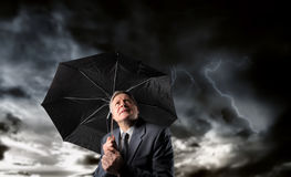 Worry. Senior businessman with umbrella under a stormy sky Stock Image