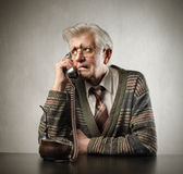 Worry. Senior man talking to telephone with worried expression Royalty Free Stock Images