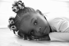 Worry. A beautiful little girl is resting on the floor.  A monochrome picture Royalty Free Stock Photo