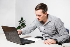 Worry businessman using laptop while sitting in office. Indicates a pen on the screen, reads important documents.  royalty free stock photo