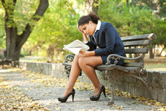 Worry businesswoman reading newspaper. Young worry businesswoman reading newspaper in park Stock Image