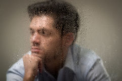 Worry depresed young man, behind a blurred window with drops, gray background.  Stock Photo