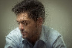 Worry depresed young man, behind a blurred window with drops, gray background.  Royalty Free Stock Photo