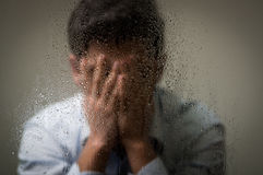 Worry depresed young man, hiding from camera using his hands, behind a blurred window with drops, gray background.  Stock Photography