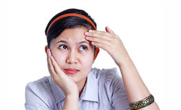 Worry Lines. Asian lady touching her worry lines in the forehead. Isolated in white background Royalty Free Stock Photos
