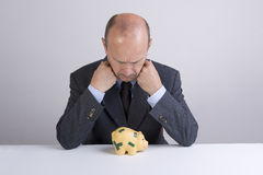 Worry. A man worry in front a piggy bank Stock Image