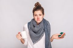 Worry puzzled woman holding cup with tea, many pills . Studio sh. Ot, isolated on gray background Stock Images