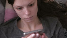 Worry woman lying on the couch and reading something at the mobile phone. Close-up face. Worry woman lying on the couch and reading something at the mobile stock video footage