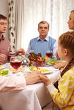 Worship. Photo of family members giving thanks to God at festive table while holding each other by hands Stock Images